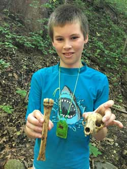 young boy holding scull and leg bone of animal